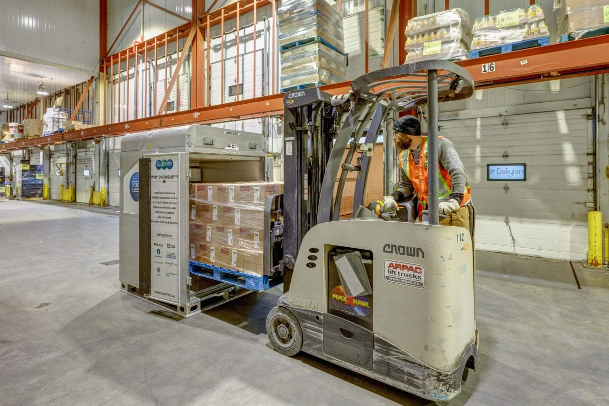 CryoLogistics SnowSHIP Unit sitting on a refrigerated warehouse dock being filled with product by a forklift